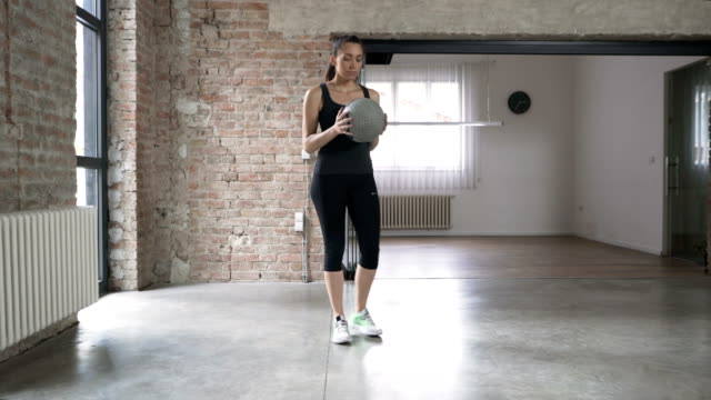 Young Woman Doing Side Lunges With Medicine Ball