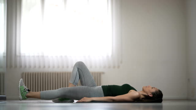 Young Woman Doing Single Leg Hip Lifts At Home