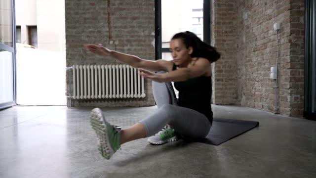 vídeos y material grabado en eventos de stock de mujer joven haciendo sola pierna stand-ups - pilates