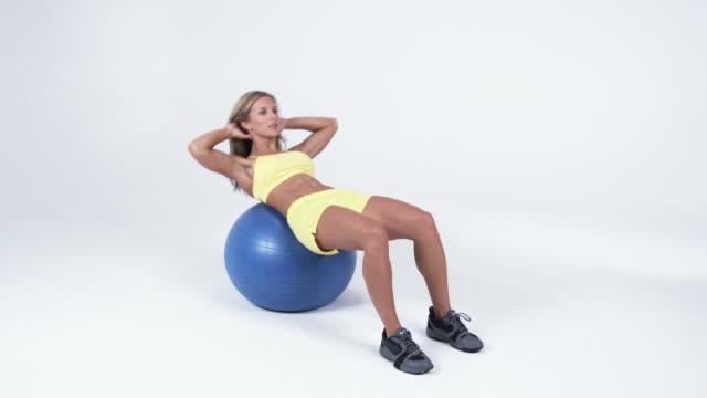 ws young woman doing sit ups on exercise ball / orem, utah, usa - orem video stock e b–roll