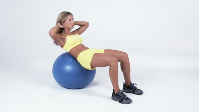 ws young woman doing sit ups on exercise ball / orem, utah, usa - pallone per fitness video stock e b–roll