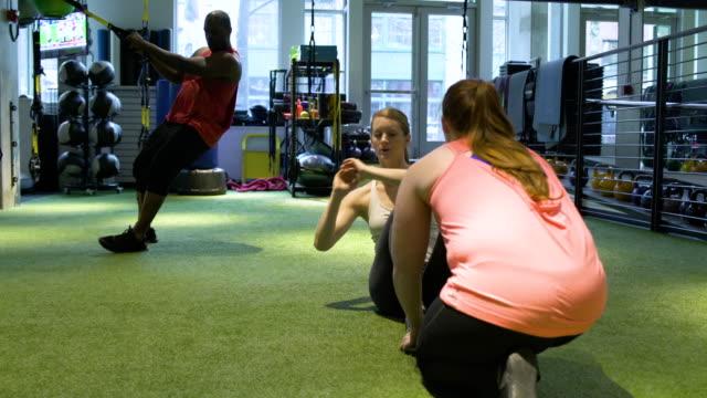 young woman doing sitting twists in a gym - 床に座る点の映像素材/bロール