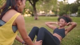 Young woman doing sit-ups with assistance of her female friend in the park - friends doing exercise in the park supporting eachother