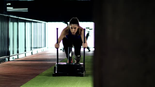 vídeos de stock e filmes b-roll de young woman doing sled pushes in the gym - empurrar atividade física