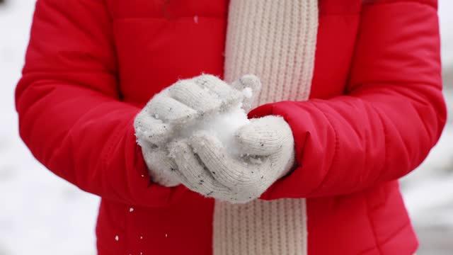 雪の下で雪玉をやっている若い女性 - ウィンターコート点の映像素材/bロール