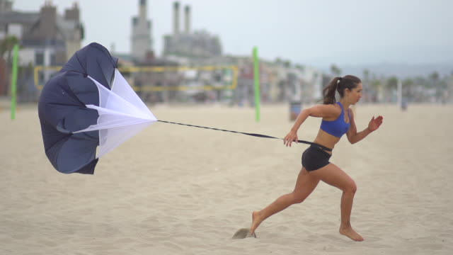 A young woman doing speed and agility training on the beach with a parachute.  - Super Slow Motion - filmed at 240 fps