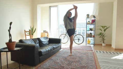 young woman doing standing splits stretching at a loft home - dance studio stock videos & royalty-free footage