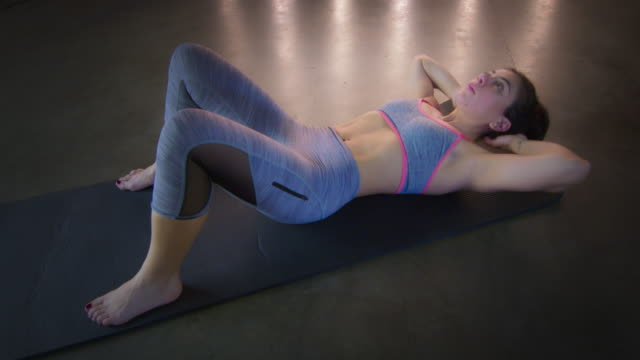 young woman doing stomach crunches on floor mat during workout 4k - vesper stock stock videos & royalty-free footage
