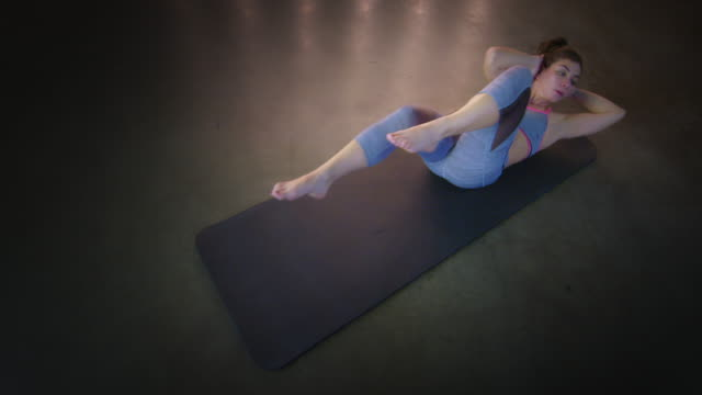 young woman doing stretches and twists on floor mat during workout 4k - vesper stock stock videos & royalty-free footage