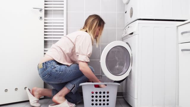 young woman doing the laundry - blonde hair stock videos & royalty-free footage