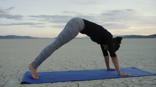 4K UHD: Young Woman Doing the Upward Facing Dog Pose while Practicing Yoga in the Desert