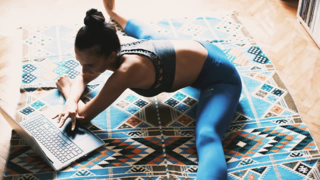 young woman doing yoga and using a laptop at home - doing the splits stock videos & royalty-free footage