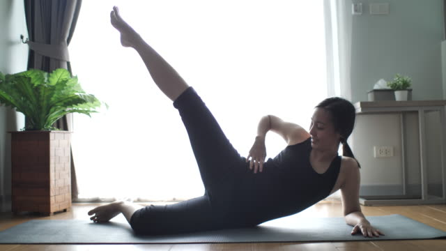 young woman doing yoga exercises at home - early morning exercise stock videos & royalty-free footage