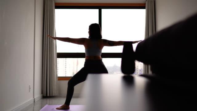 自宅の窓の前でヨガをしている若い女性 - 自制心点の映像素材/bロール