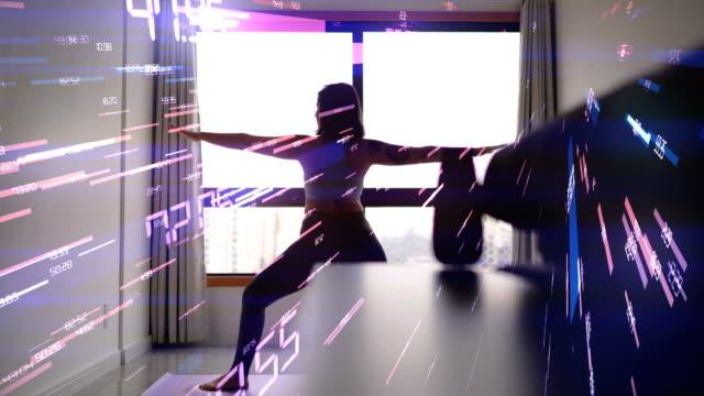 抽象的なコンピュータグラフィックス構成で自宅の窓の前でヨガをしている若い女性 - 自制心点の映像素材/bロール