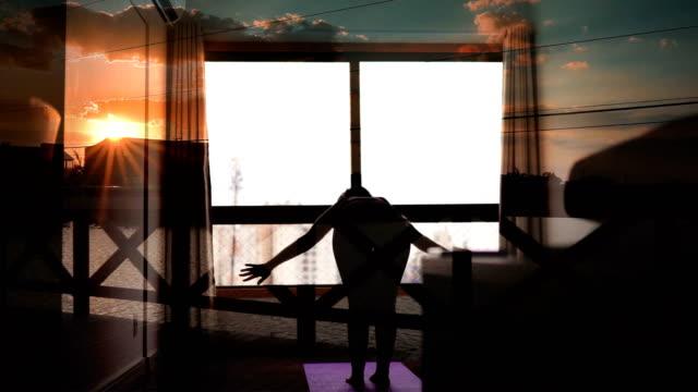 日没のオーバーレイで自宅の窓の前でヨガをしている若い女性 - 自制心点の映像素材/bロール