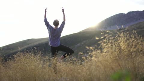 junge frau macht yoga in der natur in hohen gras auf berggipfel bei sonnenuntergang - gesunder lebensstil stock-videos und b-roll-filmmaterial