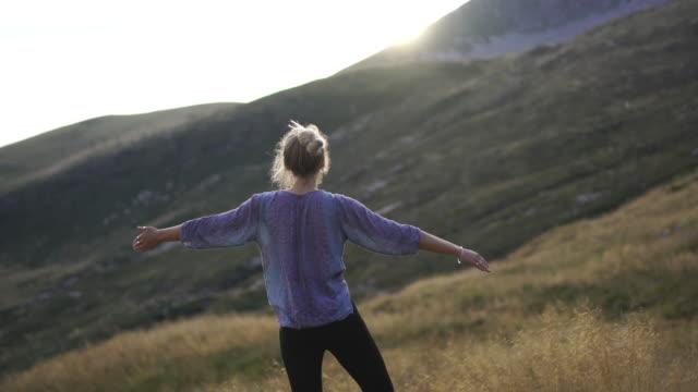 vídeos de stock, filmes e b-roll de mulher nova que faz a ioga na natureza na grama alta na parte superior da montanha no por do sol - pose de arvore