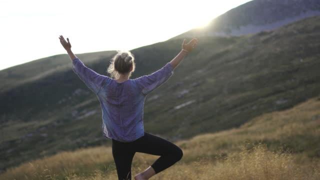 vídeos y material grabado en eventos de stock de mujer joven haciendo yoga en la naturaleza en hierba alta en la cima de la montaña al atardecer - vriksha asana