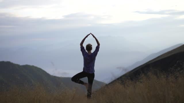 junge frau macht yoga in der natur in hohen gras auf berggipfel bei sonnenuntergang - auf einem bein stock-videos und b-roll-filmmaterial