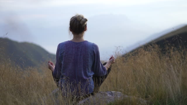 young woman doing yoga in nature in tall grass on mountain top at sunset - lotus position stock videos & royalty-free footage