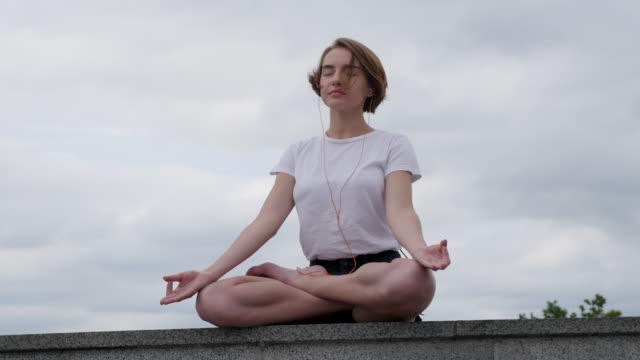 young woman doing yoga in the city - lotus position stock videos & royalty-free footage
