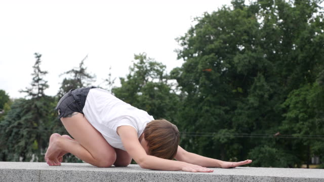 young woman doing yoga in the city - white shirt stock videos & royalty-free footage