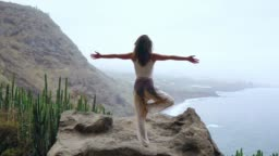Young woman doing yoga in the mountains standing on one leg overlooking the ocean.