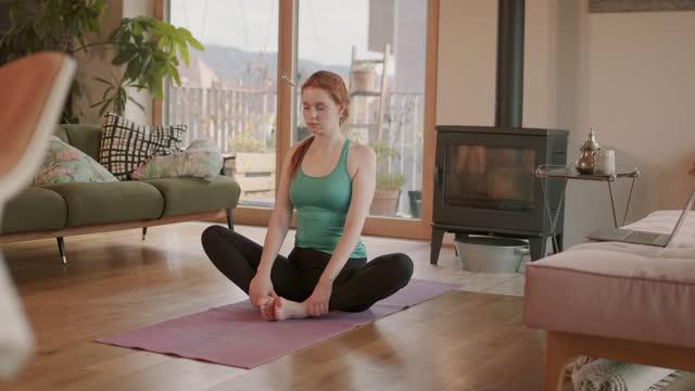 vídeos de stock e filmes b-roll de young woman doing yoga, meditating in living room - zen