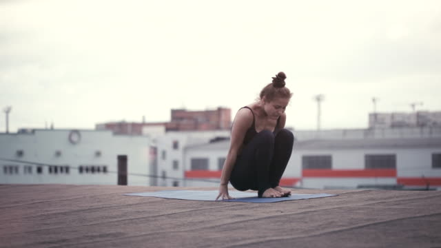 young woman doing yoga meditating outdoors on a rooftop - lotus position stock videos & royalty-free footage