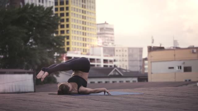 stockvideo's en b-roll-footage met jonge vrouw doet yoga buiten mediteren op een dak - in kleermakerszit