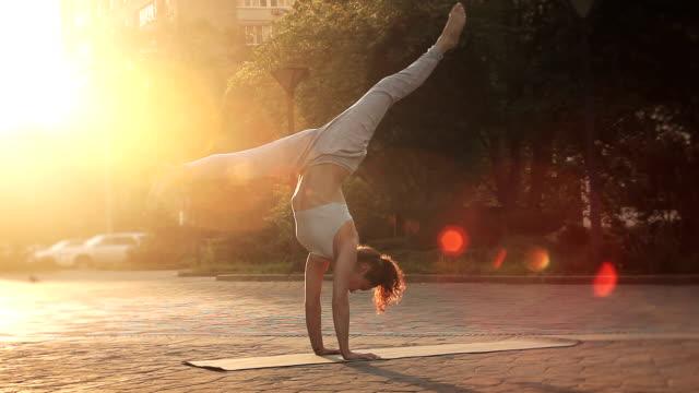 stockvideo's en b-roll-footage met jonge vrouw doen yoga meditatie oefeningen bij zonsondergang - in kleermakerszit