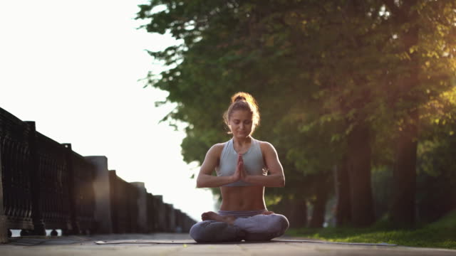 young woman doing yoga meditation exercises at sunset - lotus position stock videos and b-roll footage