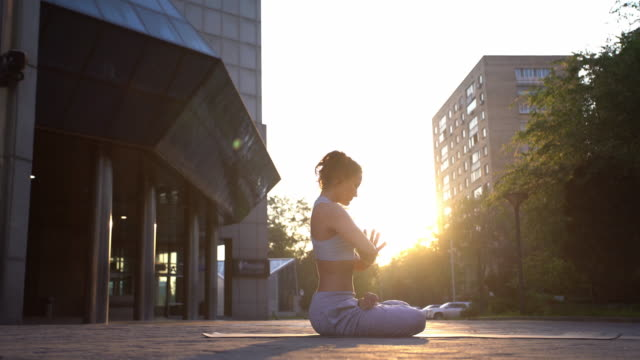 young woman doing yoga meditation exercises at sunset - lotus position stock videos & royalty-free footage