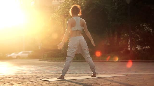 ung kvinna gör yoga meditation övningar vid solnedgången - korslagda ben bildbanksvideor och videomaterial från bakom kulisserna