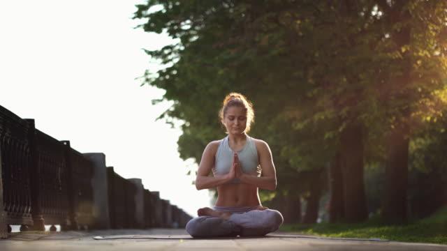 Jonge vrouw doen Yoga meditatie oefeningen bij zonsondergang