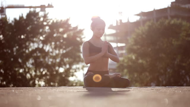 Young woman doing yoga moditating on a rooftop at sunset