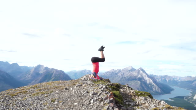 young woman doing yoga on a mountain top - oblivious stock videos & royalty-free footage