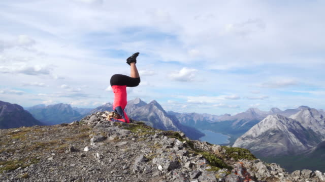 Young woman doing yoga on a mountain top