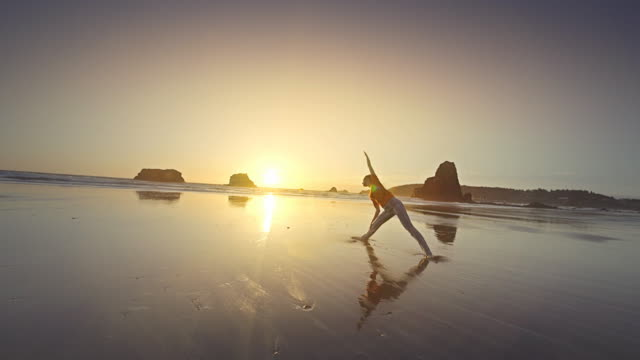 vidéos et rushes de young woman doing yoga on beach at sunset, oregon - sérénité