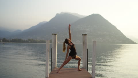young woman doing yoga on dock looking out at lake and sunrise - gesunder lebensstil stock-videos und b-roll-filmmaterial