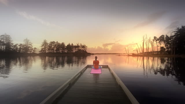 Young woman doing Yoga on dock of a lake at sunset, Oregon