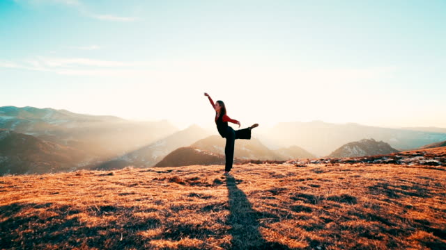 Young woman doing yoga on mountain top at sunrise