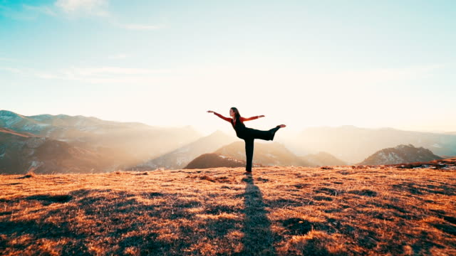 stockvideo's en b-roll-footage met young woman doing yoga on mountain top at sunrise - bergketen