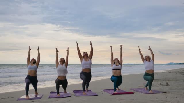 vídeos y material grabado en eventos de stock de young woman doing yoga on the beach - sólo mujeres jóvenes