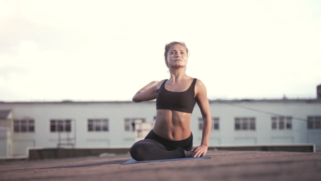 young woman doing yoga outdoors on a rooftop at sunset - lotus position stock videos & royalty-free footage