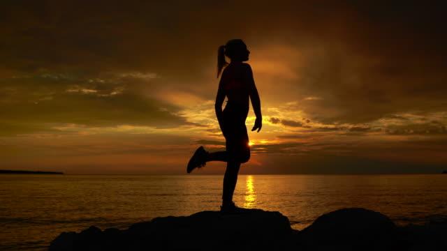 junge frau macht yoga, stehend auf einem bein bei sonnenuntergang - gleichgewicht stock-videos und b-roll-filmmaterial