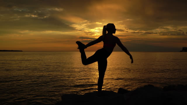 young woman doing yoga, standing on one leg during sunset - on one leg stock videos & royalty-free footage
