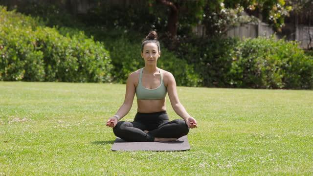vidéos et rushes de jeune femme faisant du yoga - assis en tailleur