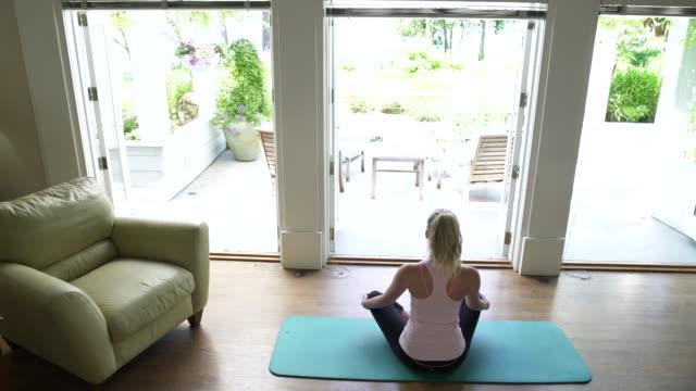 young woman doing yoga - 胡坐点の映像素材/bロール